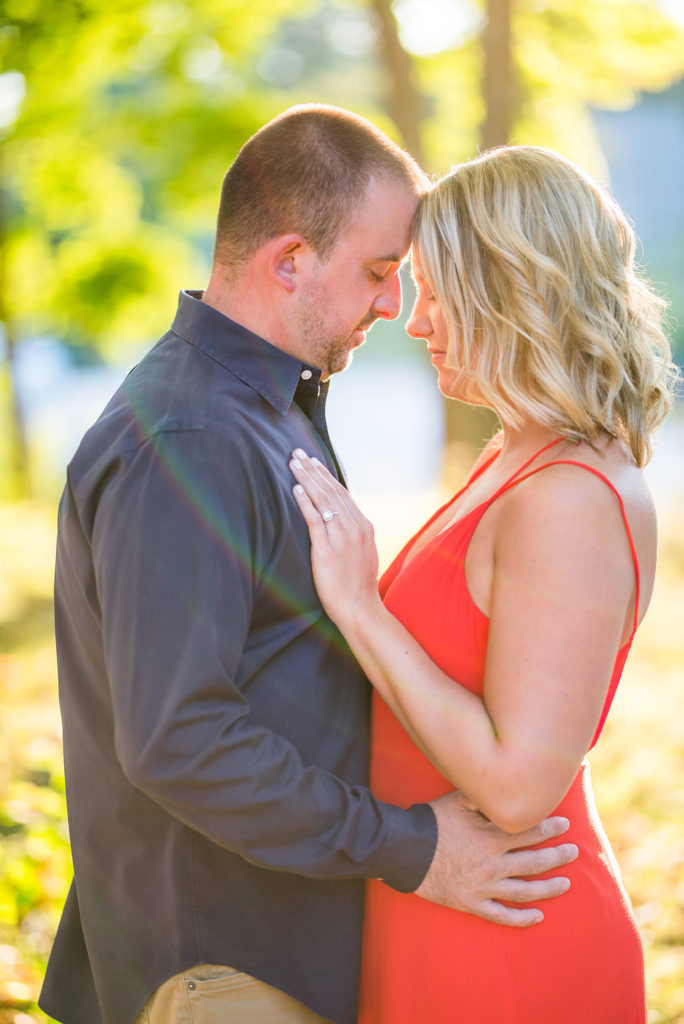 couple holding each other red dress sun flare Kaitlyn Ferris engaged