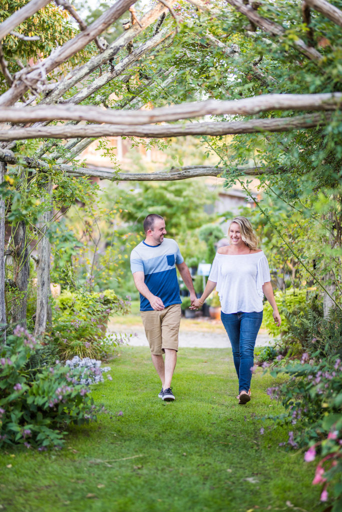 couple laughing and walking through arbor Kaitlyn Ferris engaged