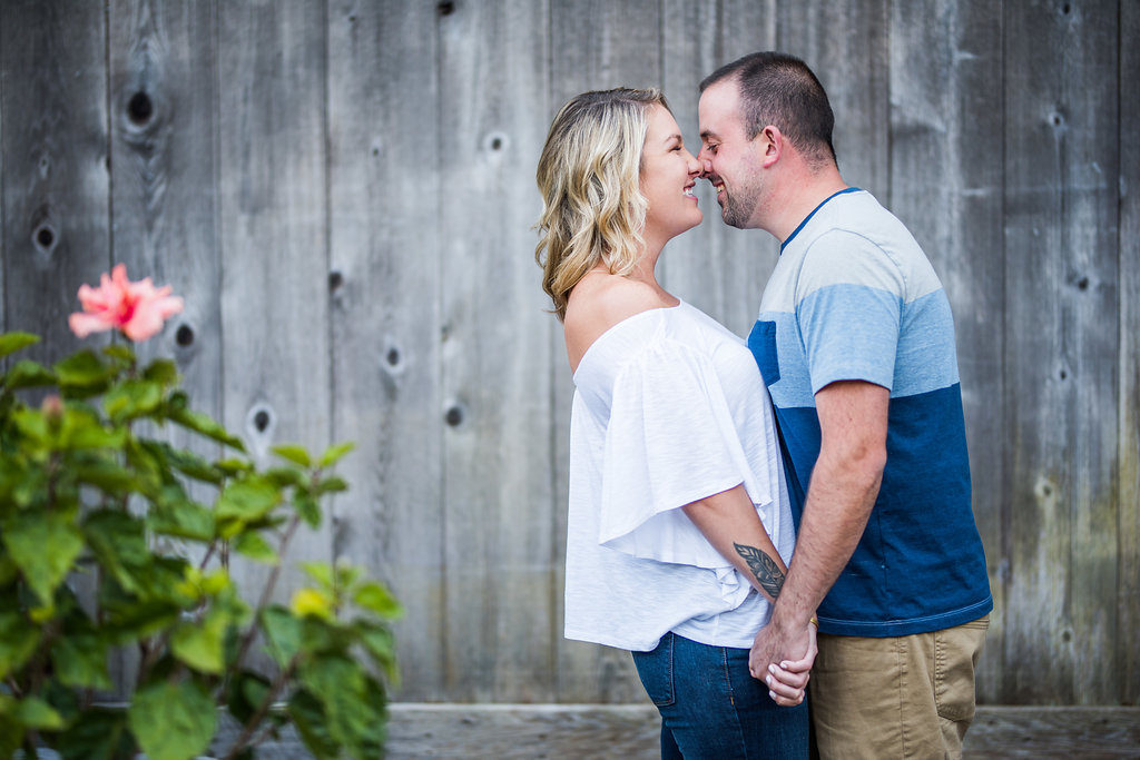 couple kissing in front of wood wall Kaitlyn Ferris engaged