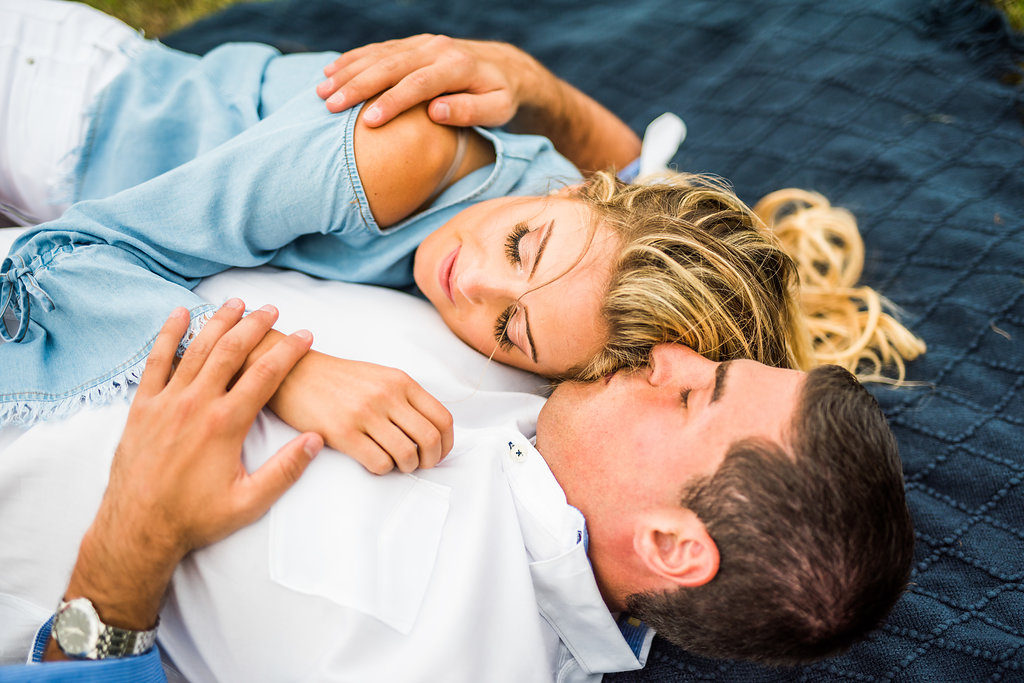 laying on a blanket kiss romantic engagement